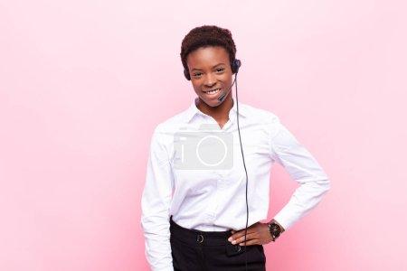 Photo pour Jeunes jolies femmes noiressouriant joyeusement avec une main sur la hanche et confiant, attitude positive, fière et amicale - image libre de droit