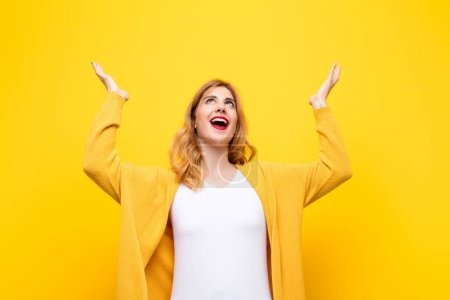 Photo for Young pretty blonde woman feeling happy, amazed, lucky and surprised, celebrating victory with both hands up in the air against yellow wall - Royalty Free Image