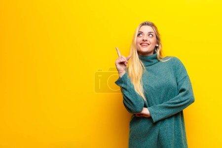 Photo for Young pretty blonde woman smiling happily and looking sideways, wondering, thinking or having an idea against yellow wall - Royalty Free Image