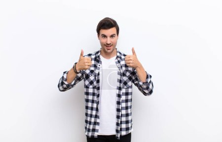 Photo for Young handsome man smiling broadly looking happy, positive, confident and successful, with both thumbs up against white wall - Royalty Free Image