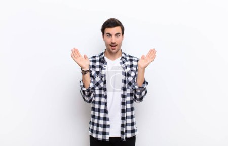 Photo for Young handsome man looking happy and excited, shocked with an unexpected surprise with both hands open next to face against white wall - Royalty Free Image