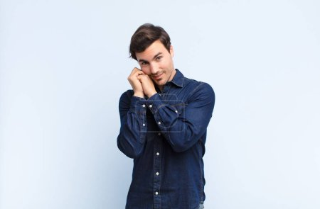 Photo for Young handsome man feeling in love and looking cute, adorable and happy, smiling romantically with hands next to face against blue wall - Royalty Free Image