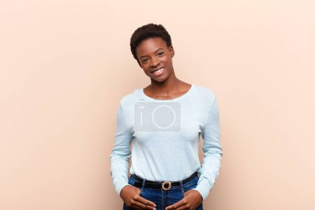 Photo for Young pretty black womansmiling cheerfully and casually with a positive, happy, confident and relaxed expression - Royalty Free Image