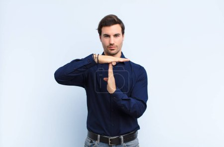 Photo for Young handsome man looking serious, stern, angry and displeased, making time out sign against blue wall - Royalty Free Image