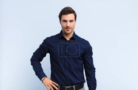 Photo for Young handsome man smiling happily with a hand on hip and confident, positive, proud and friendly attitude against blue wall - Royalty Free Image