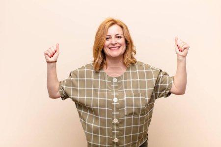 Photo pour Middle age woman feeling happy, positive and successful, celebrating victory, achievements or good luck - image libre de droit