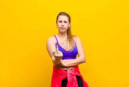 Photo pour Jeune femme blonde se sentant en colère, agacée, rebelle et agressive, retournant le majeur, se défendant. concept sportif - image libre de droit