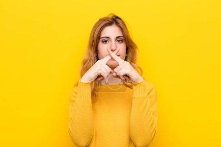 Photo pour Jeune jolie femme blonde à l'air grave et mécontente des deux doigts croisés à l'avant dans le rejet, demandant le silence contre le mur jaune - image libre de droit