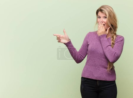 Photo for Young pretty latin woman feeling happy, shocked and surprised, covering mouth with hand and pointing to lateral copy space - Royalty Free Image