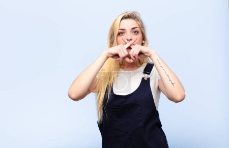 Photo pour Jeune jolie femme blonde à l'air grave et mécontente des deux doigts croisés à l'avant dans le rejet, demandant le silence contre un mur plat - image libre de droit