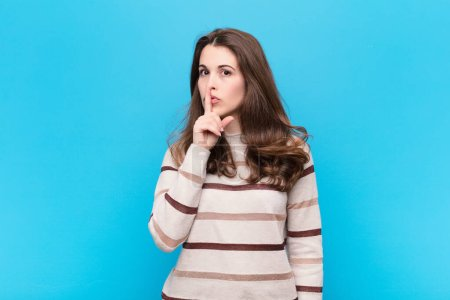 Photo for Young pretty woman asking for silence and quiet, gesturing with finger in front of mouth, saying shh or keeping a secret against blue wall - Royalty Free Image
