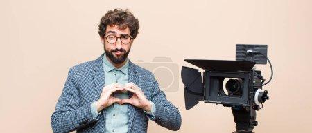 Photo pour Présentateur de télévision souriant et se sentant heureux, mignon, romantique et amoureux, faisant forme de coeur avec les deux mains - image libre de droit