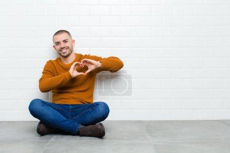 Photo pour Jeune bel homme souriant et se sentant heureux, mignon, romantique et amoureux, ce qui rend la forme du cœur avec les deux mains assises sur le sol - image libre de droit