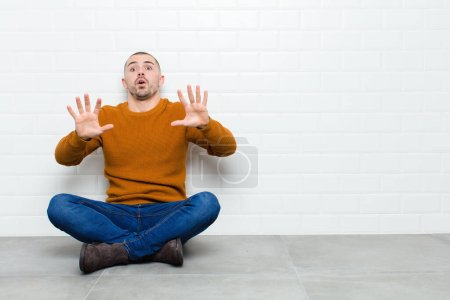 Photo for Young handsome man feeling stupefied and scared, fearing something frightening, with hands open up front saying stay away sitting on the floor - Royalty Free Image