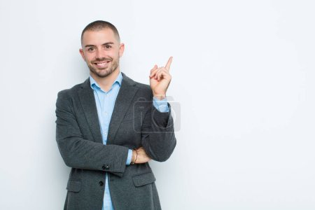 Photo pour Jeune homme d'affaires souriant joyeusement et regardant de côté, se demandant, pensant ou ayant une idée contre un mur plat - image libre de droit