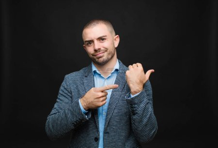 Photo for Young businessman looking impatient and angry, pointing at watch, asking for punctuality, wants to be on time against flat wall - Royalty Free Image