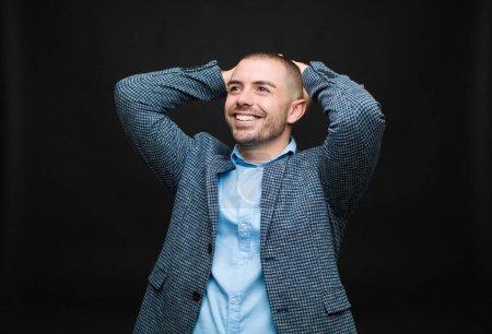 Photo pour Jeune homme d'affaires souriant et se sentant détendu, satisfait et insouciant, riant positivement et se refroidissant contre un mur plat - image libre de droit