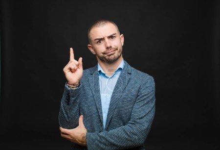 Photo pour Jeune homme d'affaires se sentant comme un génie tenant fièrement le doigt dans les airs après avoir réalisé une grande idée, disant eureka contre un mur plat - image libre de droit