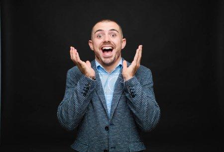 Photo pour Jeune homme d'affaires se sentant choqué et excité, riant, étonné et heureux en raison d'une surprise inattendue contre un mur plat - image libre de droit