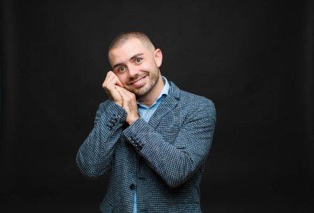 Photo pour Jeune homme d'affaires se sentant amoureux et regardant mignon, adorable et heureux, souriant romantiquement avec les mains à côté du visage contre un mur plat - image libre de droit