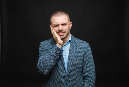 Photo for Young businessman holding cheek and suffering painful toothache, feeling ill, miserable and unhappy, looking for a dentist against flat wall - Royalty Free Image