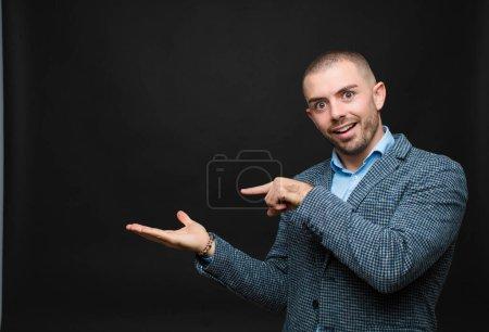 Photo pour Jeune homme d'affaires souriant joyeusement et pointant vers copier l'espace sur la paume sur le côté, montrant ou annonçant un objet contre un mur plat - image libre de droit