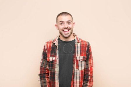 Photo for Young handsome man looking happy and pleasantly surprised, excited with a fascinated and shocked expression against flat wall - Royalty Free Image