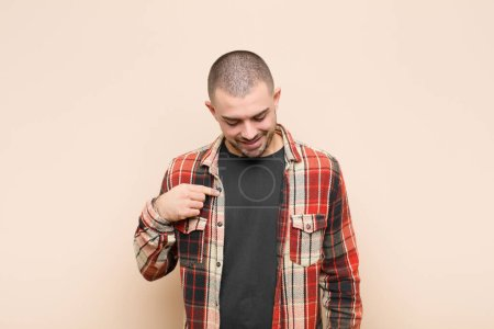 Photo for Young handsome man smiling cheerfully and casually, looking downwards and pointing to chest against flat wall - Royalty Free Image