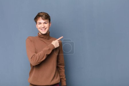 Photo for Young blonde man smiling cheerfully, feeling happy and pointing to the side and upwards, showing object in copy space isolated against flat wall - Royalty Free Image