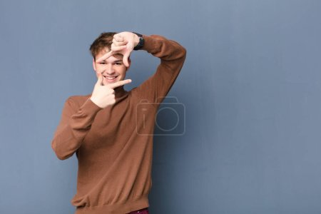 Photo for Young blonde man feeling happy, friendly and positive, smiling and making a portrait or photo frame with hands isolated against flat wall - Royalty Free Image
