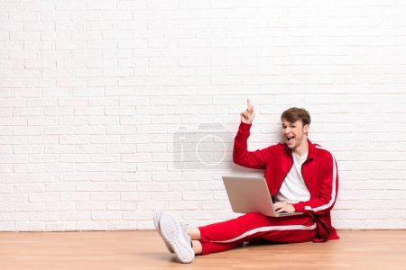 Photo for Young blonde man sitting on the floor with a laptop - Royalty Free Image