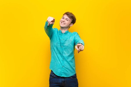 Photo for Young blonde man feeling happy and confident, pointing to camera with both hands and laughing, choosing you isolated against flat wall - Royalty Free Image