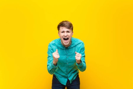 Photo for Young blonde man shouting aggressively with annoyed, frustrated, angry look and tight fists, feeling furious isolated against flat wall - Royalty Free Image