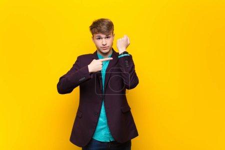 Photo pour Jeune homme blond regardant impatient et en colère, pointant vers la montre, demandant la ponctualité, veut être à l'heure isolé contre un mur plat - image libre de droit