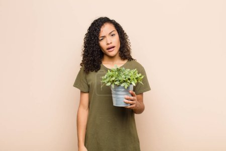 Photo for Young black woman feeling puzzled and confused, with a dumb, stunned expression looking at something unexpected holding a plant - Royalty Free Image
