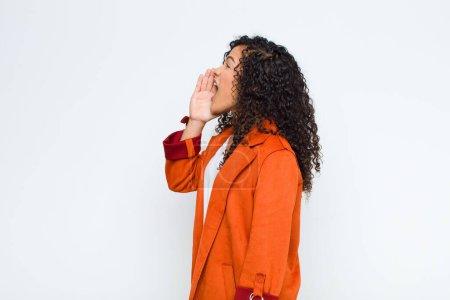 Photo pour Jeune femme noire vue de profil, regardant heureux et excité, criant et appelant à copier l'espace sur le côté contre le mur blanc - image libre de droit