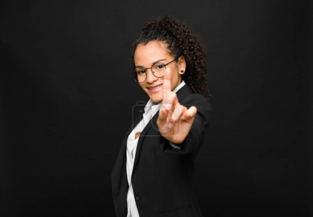 Photo for Young black woman smiling proudly and confidently making number one pose triumphantly, feeling like a leader against black wall - Royalty Free Image