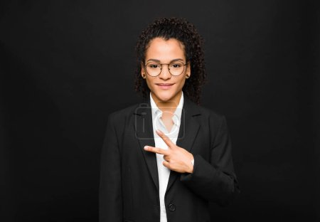 Photo pour Jeune femme noire se sentant heureuse, positive et réussie, avec la main en forme de v sur la poitrine, montrant la victoire ou la paix contre le mur noir - image libre de droit