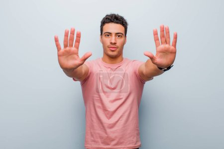 Photo for Young arabian man looking serious, unhappy, angry and displeased forbidding entry or saying stop with both open palms against gray wall - Royalty Free Image