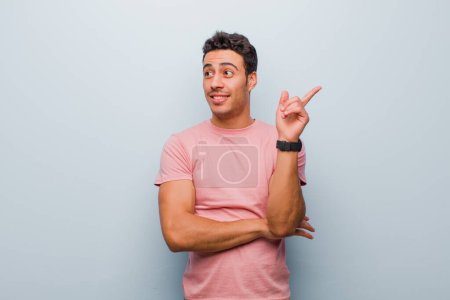 Photo for Young arabian man smiling happily and looking sideways, wondering, thinking or having an idea against gray wall - Royalty Free Image