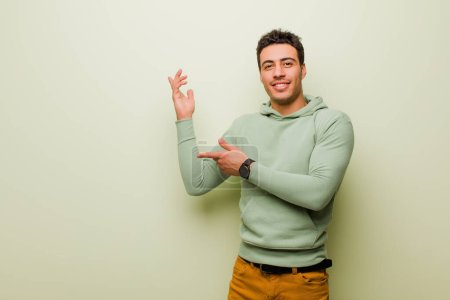 Photo for Young arabian man smiling proudly and confidently, feeling happy and satisfied and showing a concept on copy space against flat wall - Royalty Free Image