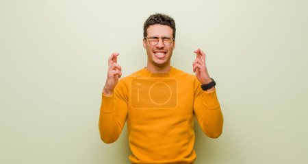 Photo for Young arabian man smiling and anxiously crossing both fingers, feeling worried and wishing or hoping for good luck against flat wall - Royalty Free Image