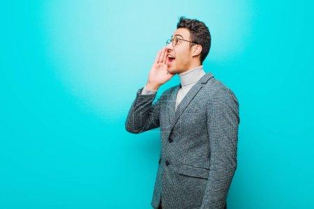 Photo pour Jeune homme arabe vue de profil, regardant heureux et excité, criant et appelant à copier l'espace sur le côté contre le mur bleu - image libre de droit