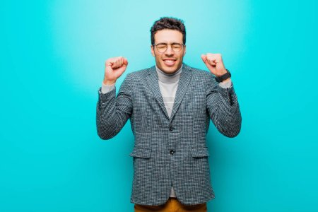 Photo for Young arabian man looking extremely happy and surprised, celebrating success, shouting and jumping against blue wall - Royalty Free Image