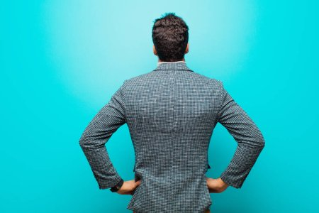 Photo for Young arabian man feeling confused or full or doubts and questions, wondering, with hands on hips, rear view against blue wall - Royalty Free Image