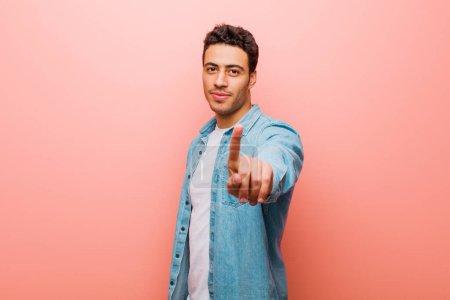 Photo pour Jeune homme arabe souriant fièrement et en toute confiance faisant la pose numéro un triomphalement, se sentant comme un leader contre le mur rose - image libre de droit