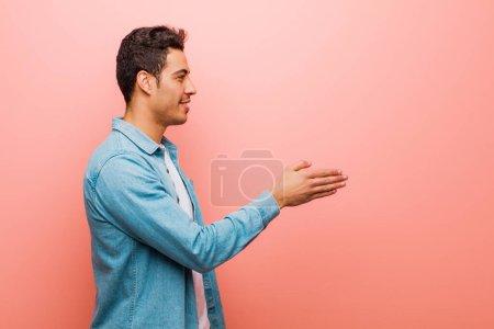Photo pour Jeune homme arabe souriant, vous saluant et vous offrant une poignée de main pour conclure un accord réussi, concept de coopération contre le mur rose - image libre de droit