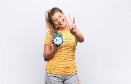 Photo pour Souriant et amical, montrant le numéro trois ou troisième avec la main vers l'avant, compte à rebours - image libre de droit