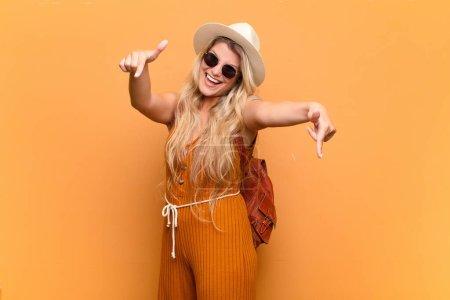 Photo pour Jeune jolie femme latine se sentant heureuse et confiante, pointant vers la caméra avec les deux mains et riant, vous choisissant. concept touristique - image libre de droit
