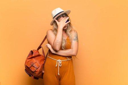 Photo pour Jeune jolie femme latine à l'air stressée, honteuse ou bouleversée, avec un mal de tête, couvrant le visage avec la main. concept touristique - image libre de droit
